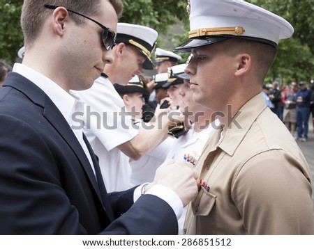 NEW YORK - MAY 22 2015: A US Marine receives his promotion insignia during the ceremony held at the National September 11 Memorial site during Fleet Week 2015. - stock photo