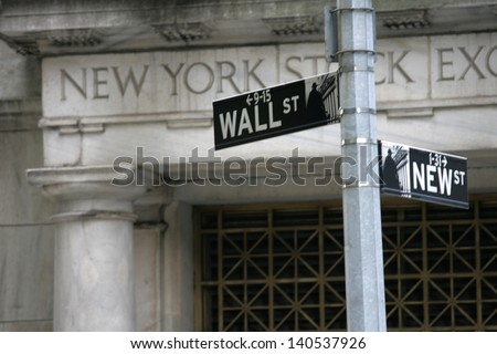 NEW YORK - MAY 30: A Wall Street street sign is shown on May 30, 2013 in New York City. The Exchange building was built in 1903. - stock photo