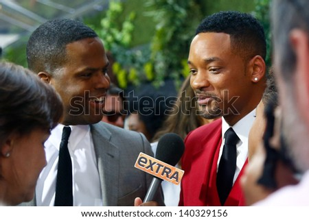 """NEW YORK - MAY 29: Actor Will Smith (R) speaks to TV personality A.J. Calloway at the premiere of """"After Earth"""" at the Ziegfeld Theatre on May 29, 2013 in New York City.  - stock photo"""