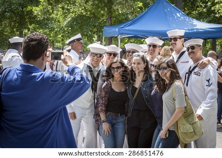 NEW YORK - MAY 22 2015: Group of young women pose with US Navy sailors gathering at the military re-enlistment and promotion ceremony at the National September 11 Memorial site during Fleet Week 2015. - stock photo