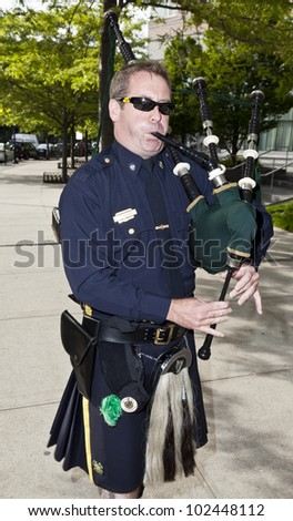 NEW YORK - MAY 12: Member of NYPD plays bag pipe outside of reception for the 2012 Ellis Island Medals of Honor at Ritz Carlton Battery Park on May 12, 2012 in New York City.