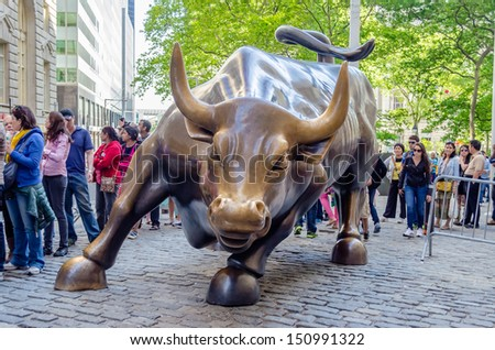 NEW YORK - MAY 27: The landmark Charging Bull in Downtown Manhattan, May 27, 2013. The sculpture is a popular tourist destination and represents aggressive financial optimism and prosperity - stock photo