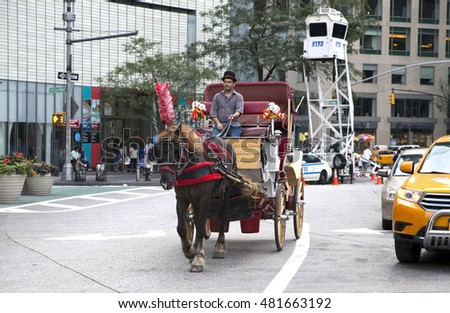 NEW YORK, NEW YORK - AUGUST 21: Man on horse drawn carriage rides through Columbus Circle.  Taken August 21, 2015 in  New York.