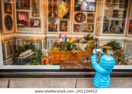 NEW YORK, NEW YORK - DECEMBER 25: A little child, holding a camera toy, taking pictures of a holiday window display at Lord & Taylor store on December 25, 2014, Christmas, in Midtown of Manhattan. - stock photo