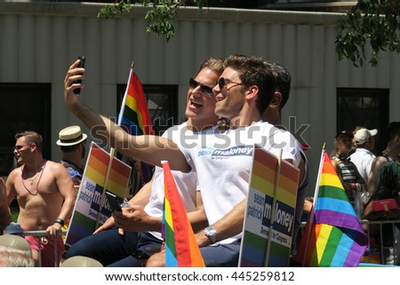NEW YORK, NEW YORK - JULY 26, 2016: Men in Gay Pride Parade taking selfies. The rainbow flag is the symbol of lesbian, gay, bisexual and transgender pride and diversity. Editorial use only. - stock photo