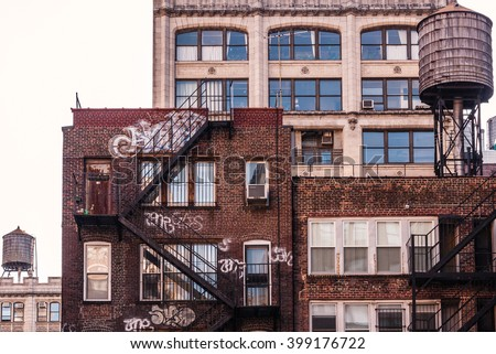 NEW YORK, NEW YORK - MAR 3:  Residential dwellings, with graffiti, in New York City, and also water tank atop the walk-up on March 3, 2012. Many of NYC's residential buildings are pre-war structures.