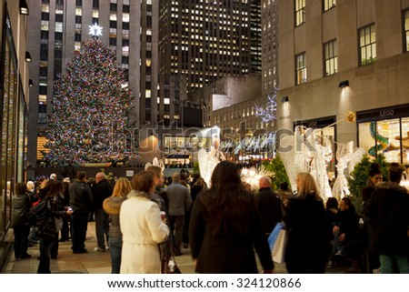 New York, New York, USA - December 1, 2011: People stroll along the plaza at Rockefeller Center during the Christmas Holiday season in the evening. The famous decorated tree can be seen. - stock photo
