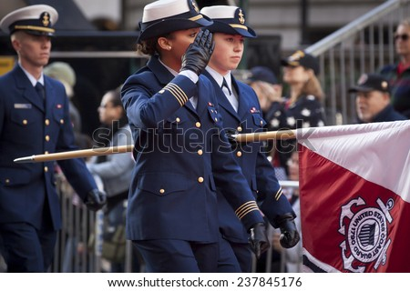 NEW YORK - NOV 11, 2014: A female captain from the US Navy salutes as she marches past the VIP stage during the 2014 America's Parade held on Veterans Day in New York City on November 11, 2014. - stock photo