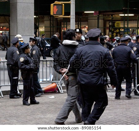 NEW YORK - NOV 17:  An unidentified man being arrested at Broad & Beaver Streets on November 17, 2011 in New York City, NY. Dubbed 'Day of Disruption', it is the 2 month mark since the movement began. - stock photo