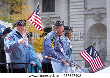NEW YORK - NOV 11, 2014: US vets wave American Flags as they stand on a parade float in the 2014 America's Parade held on Veterans Day in New York City on November 11, 2014. - stock photo