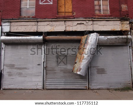 NEW YORK, NOVEMBER 3: Damaged metal doors cover closed stores on Front Street in New York City, November 3, 2012. Lower Manhattan was seriously damaged by flooding from Hurricane Sandy. - stock photo