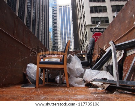 NEW YORK, NOVEMBER 3: Ruined office furniture sits in a dumpster in the Financial District of New York City, November 3, 2012. Lower Manhattan was seriously damaged by flooding from Hurricane Sandy. - stock photo