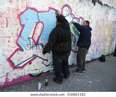NEW YORK - NOVEMBER 8, 2015: Street artists painting mural at East New York in Brooklyn. A mural is any piece of artwork painted or applied directly on a wall, ceiling or other large permanent surface - stock photo