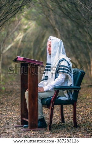 NEW YORK - NOVEMBER 3: Ultra Orthodox Jewish man praying in the forest on November 3, 2015 in New York, NY. Jewish men are obligated to pray three times daily at certain times. - stock photo
