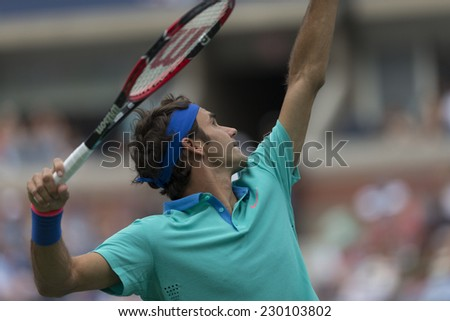 NEW YORK, NY - AUGUST 31, 2014: Roger Federer of Switzerland serves ball during 3rd round match against Marcel Granollers of Spain at US Open tennis tournament in Flushing Meadows USTA Tennis Center - stock photo