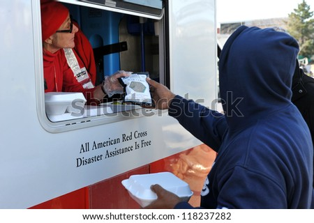 NEW YORK, NY - NOVEMBER 09: People collects hot lunches from a mobile Red Cross feeding unit in the Breezy Point part of Far Rockaway on November 9, 2012 in the Queens borough of New York City. - stock photo