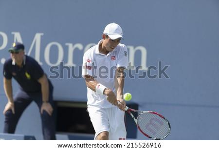 NEW YORK, NY - SEPTEMBER 6, 2014: Kei Nishikori of Japan returns ball during semifinal match against Novak Djokovic of Serbia at US Open championship in Flushing Meadows USTA Tennis Center - stock photo