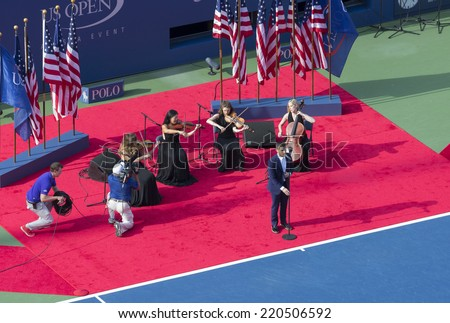 NEW YORK, NY - SEPTEMBER 7, 2014:Nick Jonas performs National Anthem before final between Caroline Wozniacki of Denmark & Serena Williams of USA at US Open championship in Flushing Meadows USTA Center - stock photo