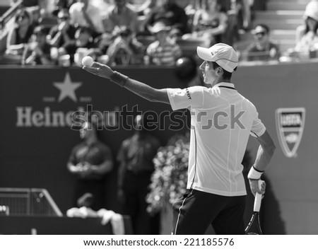 NEW YORK, NY - SEPTEMBER 6, 2014: Novak Djokovic of Serbia serves ball during semifinal match against Kei Nishikori of Japan at US Open championship in Flushing Meadows USTA Tennis Center - stock photo