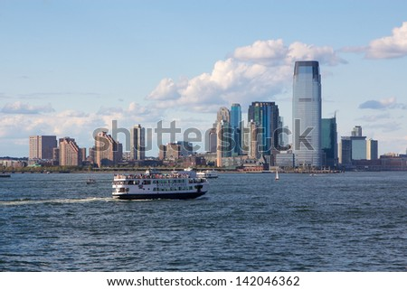 NEW YORK, NY, USA - SEPTEMBER 9: Statue Cruises ferry passes Jersey City on September 9, 2012 in New York, NY, USA. Closed since Superstorm Sandy, service to Liberty Island resumes July 2013. - stock photo