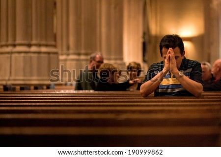 NEW YORK - OCT 20: Man prays at St Patrick's Cathedral on October 20, 2011 in New York City. The Cathedral will undergo a massive five-year, three-phase, $175 million renovation - stock photo