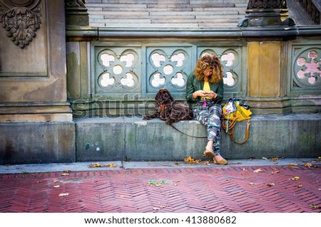 NEW YORK-OCTOBER 29: A woman with her smart phone and dog sit on a wall on October 29 2015 in Central Park. - stock photo