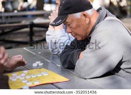 NEW YORK, October 21, 2015 - Old people playing game of Chinese mahjong outdoors - stock photo