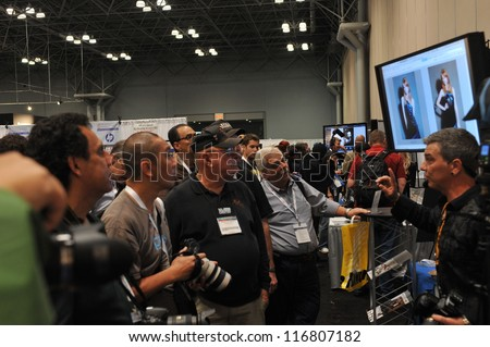 NEW YORK - OCTOBER 26: People attending the PDN PhotoPlus Expo is the largest photography show in North America, was held at the Jacob K Javits Convention Center on October 26, 2012 in New York City - stock photo
