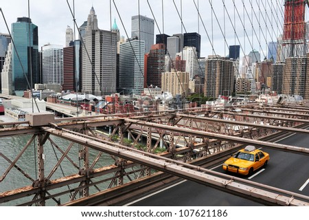 NEW YORK - OCTOBER 10: Yellow taxicab drive over Brooklyn Bridge on October 10 2009. Brooklyn Bridge completed in 1883 and it is one of the oldest suspension bridges in the United States. - stock photo