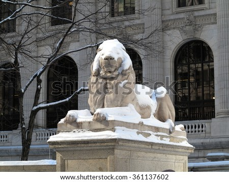 New York Public Library Lion in Winter. A snow covered stone lion at the Manhattan Library branch on 42nd Street.. - stock photo