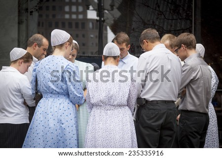 NEW YORK - SEPT 11, 2014: A group of men and women from the Pioneer Valley Mennonite Fellowship pray in front of the Millennium Hilton near the WTC site on the anniversary of the Sept 11th attacks. - stock photo