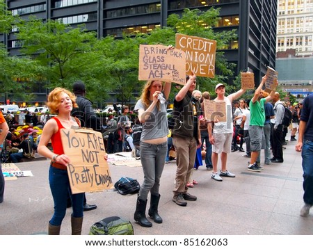 NEW YORK - SEPT. 21: A group of young people hold signs and shout messages at the Occupy Wall Street demonstration  near the New York Stock Exchange on September 21, 2011 in New York City. - stock photo