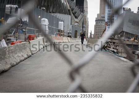NEW YORK - SEPT 11, 2014: A New York City Policeman walks through the construction zone at the One World Trade Center building in Lower Manhattan, as seen through the safety fence.  - stock photo