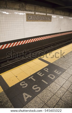 NEW YORK - SEPT 11 2016: The words Step Aside made of tiles inlaid on the platform floor near the train tracks at Grand Central Station in the New York Subway.