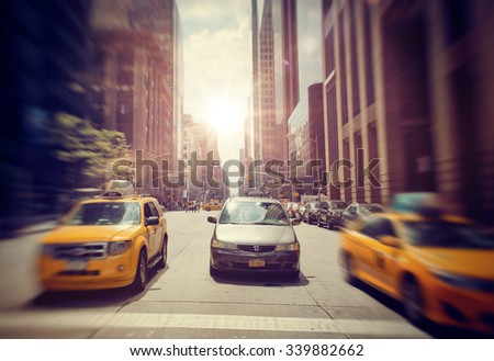 NEW YORK - SEPTEMBER 06: Front View of Sedan Driving on Urban City Street Between Two Speeding Yellow Taxi Cabs with Bright Sun Shining in Background  in New York City, USA. September 06 2015. - stock photo