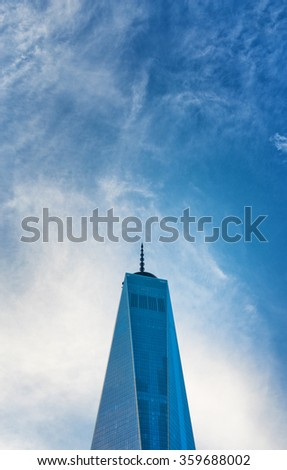 NEW YORK - SEPTEMBER 06: One World Trade Center, New York, glass facade against a blue sky with wispy cloud and copy space above. September 06, 2015 in New York. - stock photo