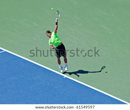 NEW YORK - SEPTEMBER 11: Rafael Nadal of Spain hits a serve during his semi-final match against Russian Mikhail Youzhny at the US Open tennis tournament on September 11, 2010, New York. - stock photo