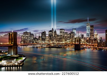 NEW YORK - SEPTEMBER 11, 2014: Tribute in Light memorial, Brooklyn Bridge and the Lower Manhattan skyline at dusk. A boat leaves colorful light trails on the Hudson River. - stock photo