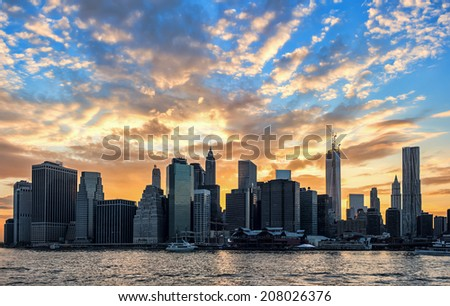 New York Skyline with powerful backlit cloudy sunset - stock photo