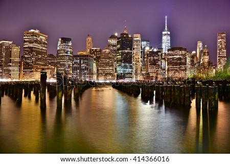 NEW YORK, UNITED STATES - DECEMBER 30, 2015 - landscape of skyscrapers from the big night brooklyn bridge lit by pilar