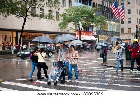 NEW YORK, UNITED STATES OF AMERICA - OCTOBER 17, 2011 : Unidentified people under rain in Fifth Avenue in New York on October 17, 2011. - stock photo