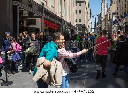 NEW YORK, USA - Apr 30, 2016: Young couple doing selfie on the streets of NYC. Manhattan street scene. The Americans on the streets of New York City