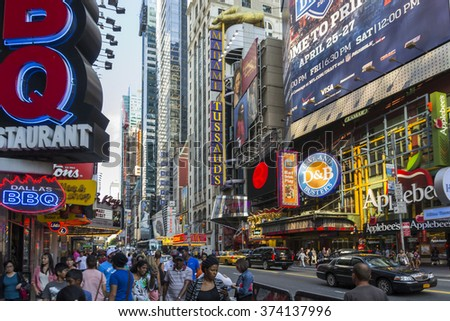 NEW YORK,USA-AUGUST 6,2013:People stroll on Times Square on a bright afternoon.Times Square is full of bright illuminated signage. - stock photo