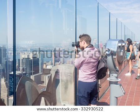 NEW YORK,USA - AUGUST 15,2015 : Tourist taking photographs from an observation deck atop a skyscraper in New York City - stock photo