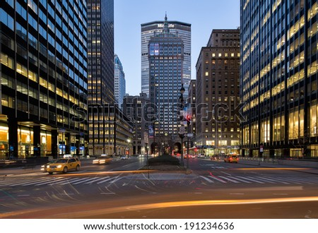 NEW YORK, USA - MARCH 18: Symmetrical composition of the illuminated Metlife building at night on Fifth Park Avenue with many light trails of cars and yellow cabs, on March 18, 2014 in New York, USA. - stock photo