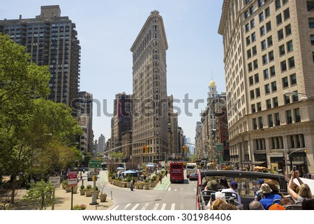 NEW YORK, USA - MAY 27, 2015: Flat Iron building facade with tourists in bus. New York, USA on May 27, 2015. Completed in 1902, it is considered to be one of the first skyscrapers ever built.  - stock photo