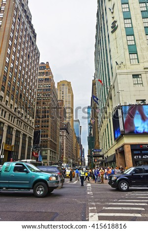 New York, USA - May 6, 2015: Intersection of West 34th Street and 7th avenue, or Fashion Avenue, and traffic policeman in Midtown Manhattan, New York City, USA. Tourists in the street. Selective focus