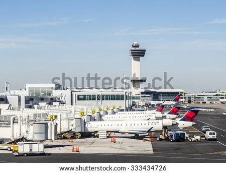 NEW YORK, USA - OCT 20, 2015: Air Traffic Control Tower and Terminal 4 with Delta Air planes at the gates in JFK Airport in NY. 1963 the airport was rededicated John F. Kennedy International Airport.
