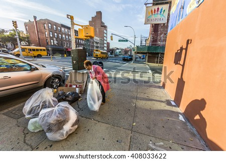 NEW YORK, USA - OCT 21, 2015: woman poses garbage at the street in Brooklyn, New York. Poverty is a main social issue in New York and many people life from collecting garbage.