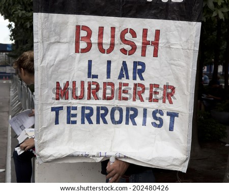 New York, USA - September 11th 2011: A man holding a sign protesting against the ex USA President George Bush on september 11th 2001 10th anniversary ceremony in Ground zero - stock photo